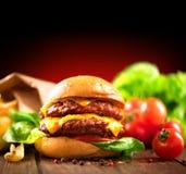 双重乳酪汉堡用新鲜的沙拉和炸薯条 免版税库存图片