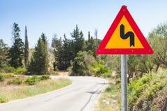 双重弯,三角黄色警告roadsign 库存照片