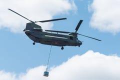 双重电动子,重的空运,军用直升机,在飞行中运载的货物 免版税库存照片