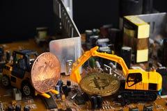 反向铲和铲车在mainboard的开掘bitcoin 免版税库存图片