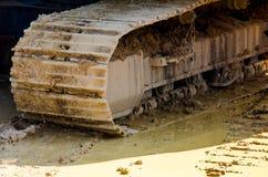 反向铲在湿泥的履带牵引装置逗留 免版税库存图片