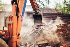 反向铲拆毁废墟,毁坏的和装载的残骸的挖掘机瓢 免版税库存图片