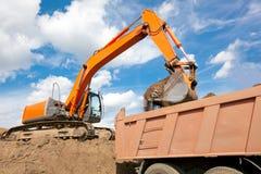 反向铲装载土壤到翻斗车机体里 库存照片