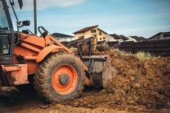 反向铲装载者关闭 成水平地球和土壤的工程师画象在环境美化的庭院里 免版税库存图片