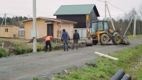 反向铲装载者开掘的土壤 工作者开掘与铁锹 放置户外站点的砖建筑 股票录像