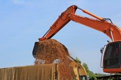 反向铲装货木片到卡车里 免版税库存图片