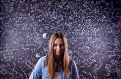反对一个大黑板的学生有数学符号的 免版税图库摄影