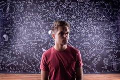 反对一个大黑板的学生有数学符号的 图库摄影
