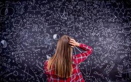 反对一个大黑板的学生有数学符号的 库存照片