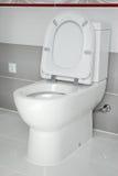 反对一个白色瓦片的马桶在卫生间里 免版税库存照片