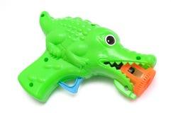 反对一个白色背景的绿色鳄鱼玩具声音枪 免版税库存照片