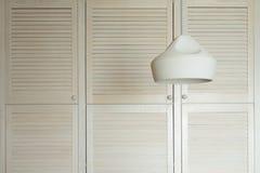 反对一个白色衣橱的枝形吊灯由自然木头制成 创造性的葡萄酒背景 库存照片
