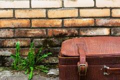 反对一个肮脏的砖墙的背景的老破旧的手提箱 免版税库存图片