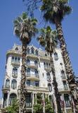 反对一个蓝天和大厦的棕榈树与稀薄的云彩在巴塞罗那,西班牙 美好的蓝色晴天 3d横向本质棕榈树 库存照片