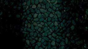 反对一个黑暗的石底下水池的红色和银色小井 库存图片