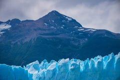 反对一座巨大的山的背景的蓝色冰川 Shevelev 免版税库存图片