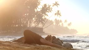 反对不尽的海洋的年轻俏丽的妇女实践瑜伽 影视素材
