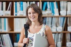 反对书架的女学生有片剂个人计算机的和袋子在图书馆里 免版税库存图片