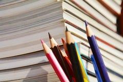 反对书背景的五颜六色的铅笔 免版税库存照片