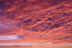 反对云彩的红色太阳 免版税库存照片