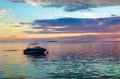 反对五颜六色的日落的小船在海洋 库存照片