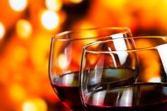 反对五颜六色的未聚焦的光背景的两块红葡萄酒玻璃 免版税库存图片