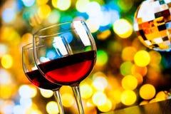 反对五颜六色的bokeh光和闪耀的迪斯科球背景的两块红葡萄酒玻璃 免版税库存照片