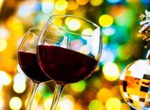 反对五颜六色的bokeh光和闪耀的迪斯科球背景的两块红葡萄酒玻璃 免版税库存图片