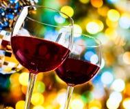 反对五颜六色的bokeh光和闪耀的迪斯科球背景的红葡萄酒玻璃 免版税库存图片