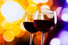 反对五颜六色的bokeh的两块红葡萄酒玻璃点燃背景 免版税库存照片