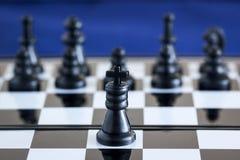 反对他的军队背景的黑人棋国王  库存照片