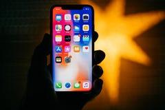 反对以家庭apps为特色的蓝色defocused星的新的苹果计算机iPhone 库存照片