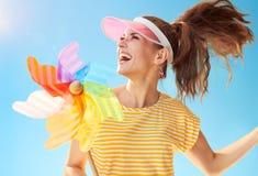 反对使用与五颜六色的风车的蓝天的快乐的妇女 免版税库存照片