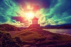 反对剧烈的多云天空的灯塔在日落期间 免版税库存照片