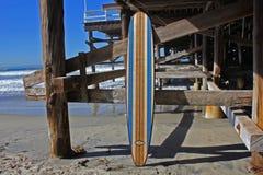 反对加利福尼亚海滩码头的木冲浪板 免版税库存照片