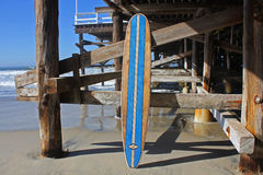 反对加利福尼亚海滩码头的木冲浪板 库存照片