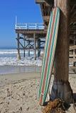 反对加利福尼亚海滩码头的木冲浪板 免版税库存图片