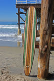 反对加利福尼亚海滩码头的木冲浪板 免版税图库摄影