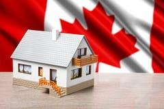 反对加拿大旗子背景的经典房子 免版税库存照片
