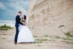 反对含沙事业的年轻时髦的婚礼夫妇在多云天空 免版税库存图片