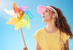 反对吹在五颜六色的风车的蓝天的微笑的适合的妇女 免版税库存图片