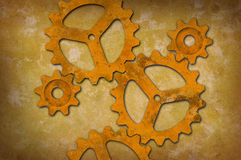 反对呈杂色的淡黄色背景的生锈的齿轮 免版税库存照片