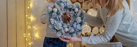反对国内欢乐背景的愉快的母亲和婴孩藏品中看不中用的物品与圣诞树 孩子拿着在的圣诞节花圈 免版税库存图片