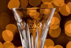 反对圣诞树光的水晶香槟槽 免版税库存图片