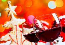 反对圣诞树背景的两块红葡萄酒玻璃 库存照片