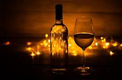 反对圣诞灯的白葡萄酒玻璃 免版税图库摄影