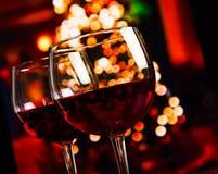 反对圣诞灯装饰背景的两块红葡萄酒玻璃 免版税库存图片