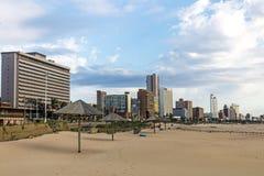 反对城市和蓝色多云地平线的早期的Moning海滩 库存照片