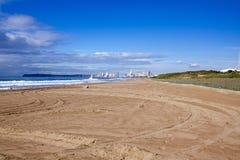 反对城市地平线和蓝色多云天空的空的海滩 库存照片