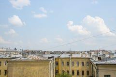 反对城市的天空蔚蓝和屋顶的美丽和强有力的云彩 库存图片